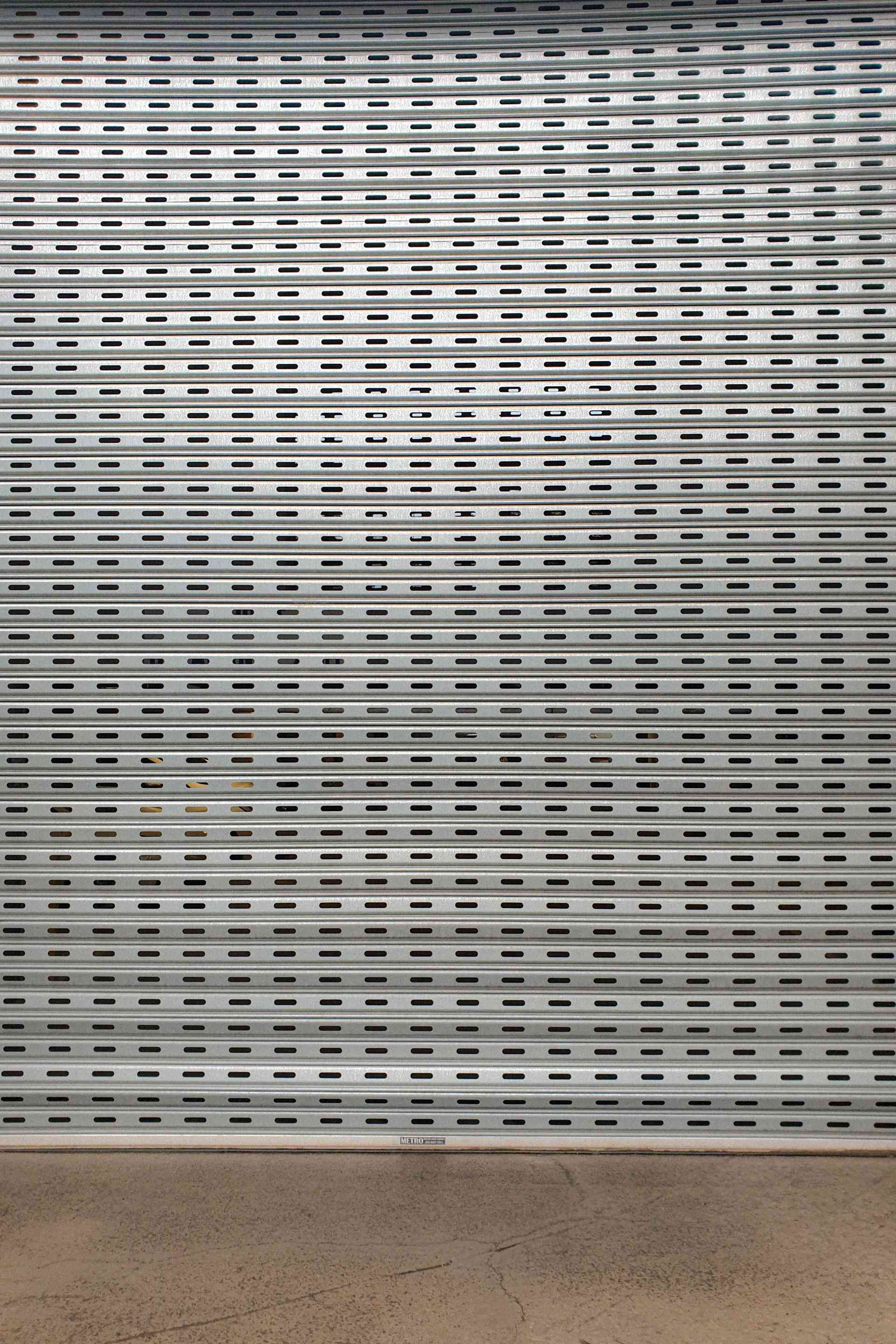 photo of a silver, perforated roller shutter with a small area of brown polished concrete visible below it